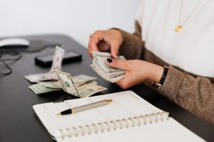 A woman with a notebook counting money at a desk.